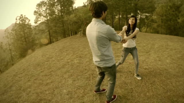 Affectionate multiethnic young couple spinning together in hills. video