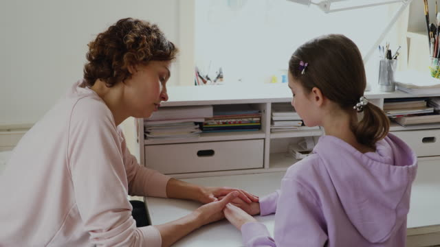 Affectionate worrying mom giving psychological help to teen daughter.