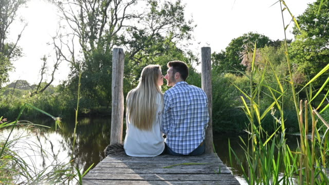 Affectionate young couple sitting together on rural pier