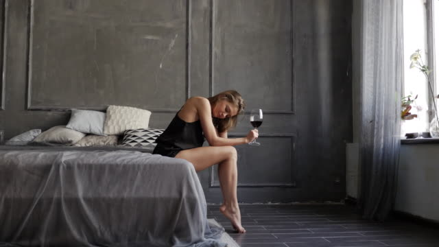 Affectionate young girl drinking wine from big glass