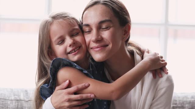 affectionate junge mutter umarmung niedlichen kind tochter genießen zärtlichen moment - menschlicher kopf stock-videos und b-roll-filmmaterial