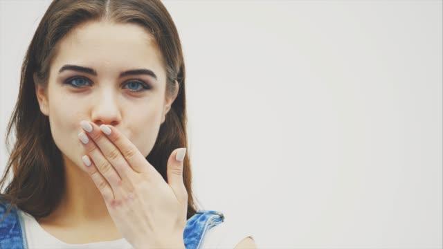 tillgiven ung kvinna med stora blå ögon blåser luft kyss, hon är klädd i casual kläder, har naturlig makeup. - blåsa en kyss bildbanksvideor och videomaterial från bakom kulisserna
