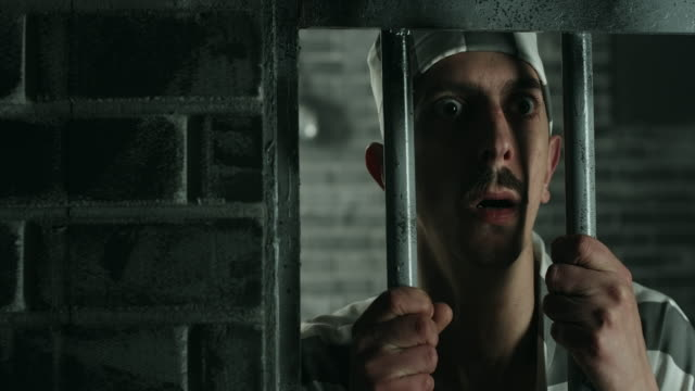 Afraid men holding prison bars at prison cell video