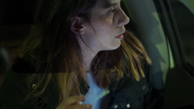 adolescente spaventata con lividi sul viso che fuma in macchina - sigaretta video stock e b–roll