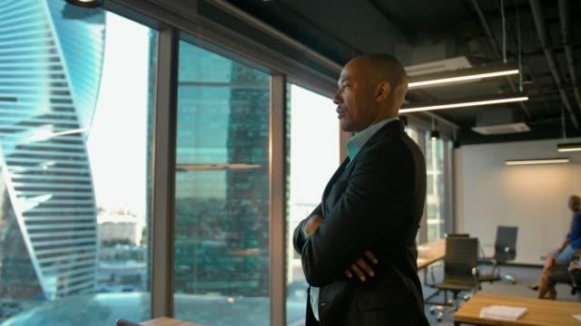 stockvideo's en b-roll-footage met aframerican ondernemer staande in de buurt van grote moderne kantoor venster met ernstige expressie - afro amerikaanse etniciteit