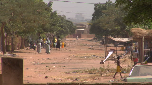 Africa street scene A typical hot day in an African city. Boys playing soccer and people casually walking. poverty stock videos & royalty-free footage