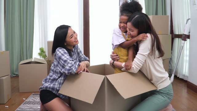 afrikansk adopterad dotter överraskar ung asiatisk hbtq-kvinna genom att hoppa inifrån en papperslåda, kramas i ett nytt hem i flyttdagen, upprymd leende, glad. modern familj med homosexuella par och döttrar flytta på nya hem koncept. - enbarnsfamilj bildbanksvideor och videomaterial från bakom kulisserna