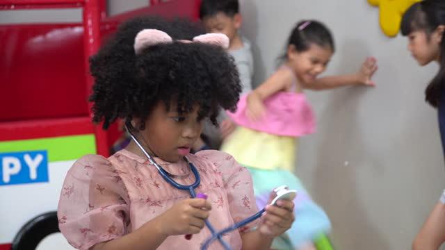 afro afro afro afro afro afro giocare un medico con stetoscopio in parco giochi per bambini al chiuso nella nursery room all'asilo - afro video stock e b–roll