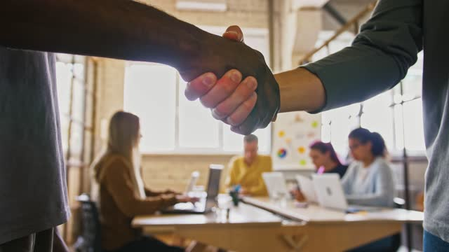 African american and caucasian businessman shaking hands as gesture of agreement and deal, close up