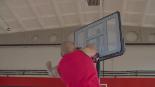 African american athlete slam dunking basketball