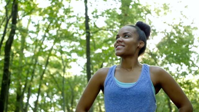 афро-американский спортивный женский бегун остановки тренировка для отдыха и проверка пульса - спортивный бюстгальтер стоковые видео и кадры b-roll