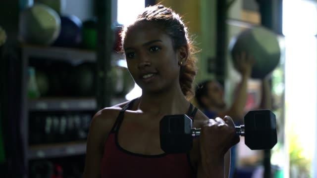 체육관에서 운동 하는 아프리카계 미국인 아름 다운 여자 - 보디 빌딩 스톡 비디오 및 b-롤 화면