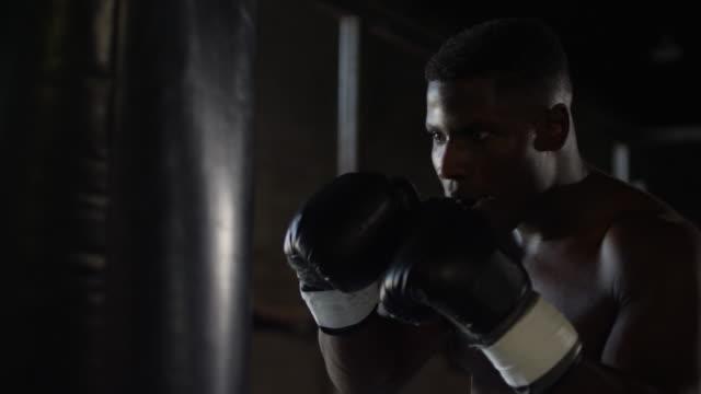 vidéos et rushes de boxeur afro-américain frappe sac lourd au ralenti - arts martiaux