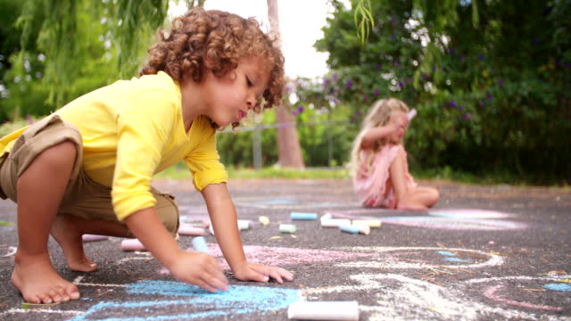 African american boy drawing chalk pictures on a park walkway video