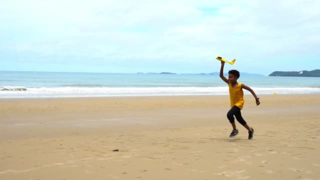 African American boy in yellow tank top run on beach with toy plane