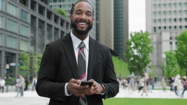 Afro-Amerikaanse zakenman met behulp van slimme telefoon onderweg video