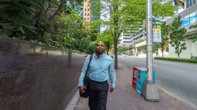 African American Businessman Walking on City Sidewalk video