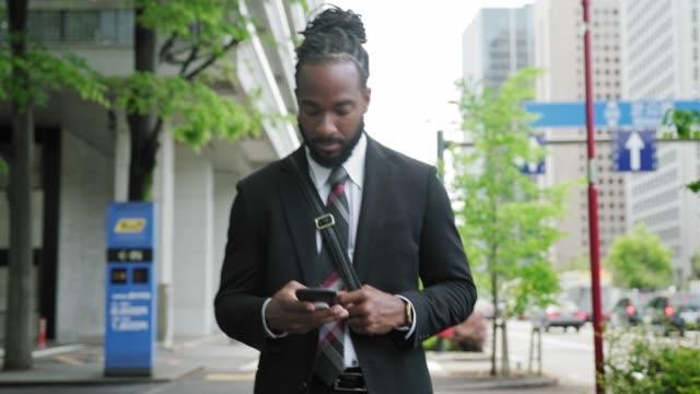Afro-Amerikaanse zakenman met een koffer met behulp van een slimme telefoon in de straten van Tokio video