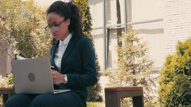 afroamerikanische geschäftsfrau trinkt kaffee und mit laptop auf bank im freien - weibliche angestellte stock-videos und b-roll-filmmaterial