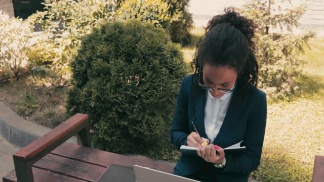 afroamerikanische geschäftsfrau mit notebook und laptop auf bank auf urbaner straße - weibliche angestellte stock-videos und b-roll-filmmaterial