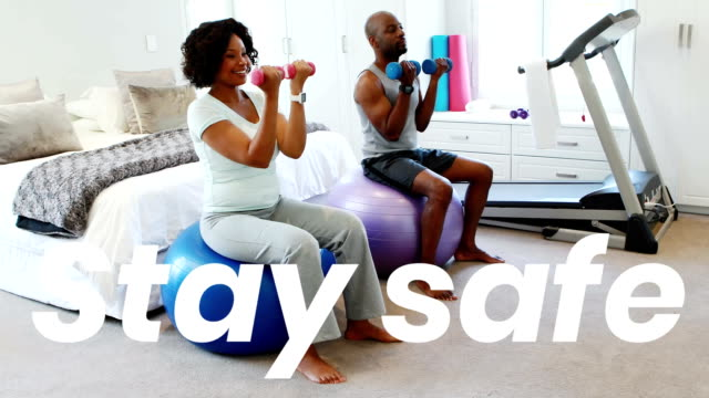 African American couple doing sport at home with words Stay Safe during coronavirus covid19 pandemic