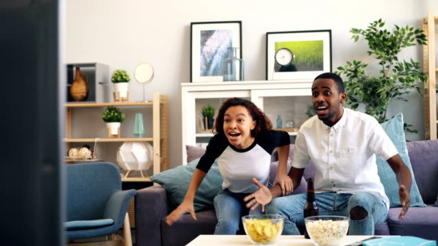 African American couple enjoying sports on TV hugging and laughing having fun African American couple man and woman are enjoying sports on TV hugging and laughing having fun after victory. Relationship, television and lifestyle concept. cheering stock videos & royalty-free footage