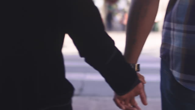 African American couple holding hands and walking, close up on their hands video