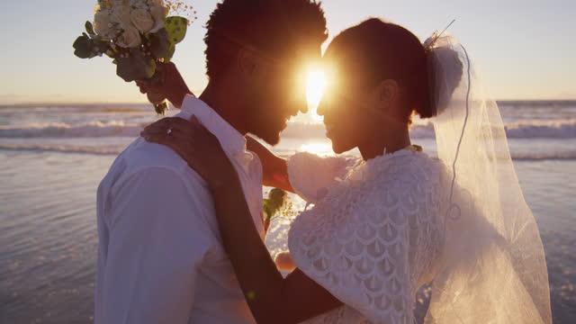 vídeos de stock, filmes e b-roll de casal afro-americano apaixonado por se casar, olhando um para o outro na praia ao pôr do sol - casamento
