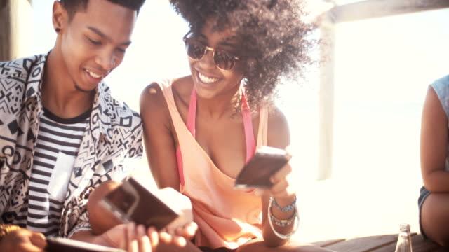 stockvideo's en b-roll-footage met african american couple sharing photographs of fun memories - polaroid
