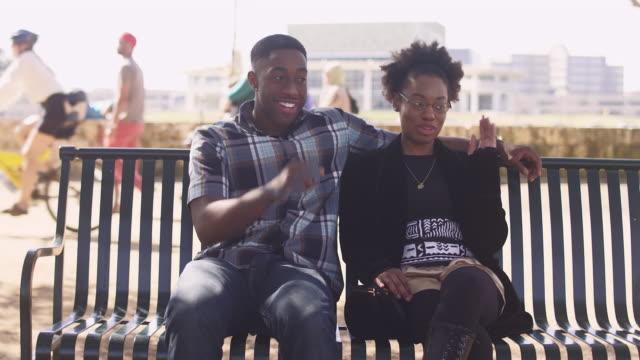 アフリカ系アメリカ人カップルは都市のウォーター フロントにベンチに一緒に座って、離れてハエをたたく - ハエ点の映像素材/bロール