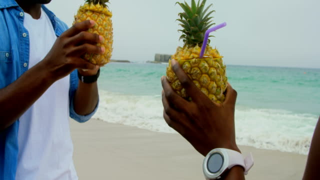 African american couple toasting pineapple juices on the beach 4k