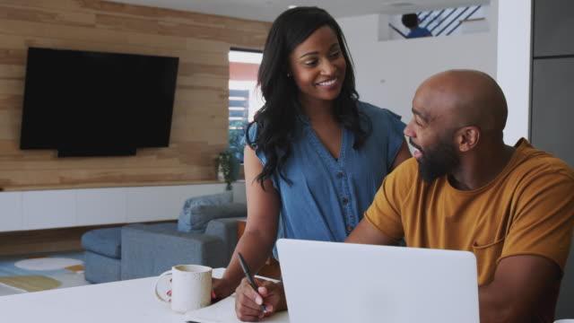 coppia afroamericana che usa laptop per controllare le finanze a casa - fare una prenotazione video stock e b–roll