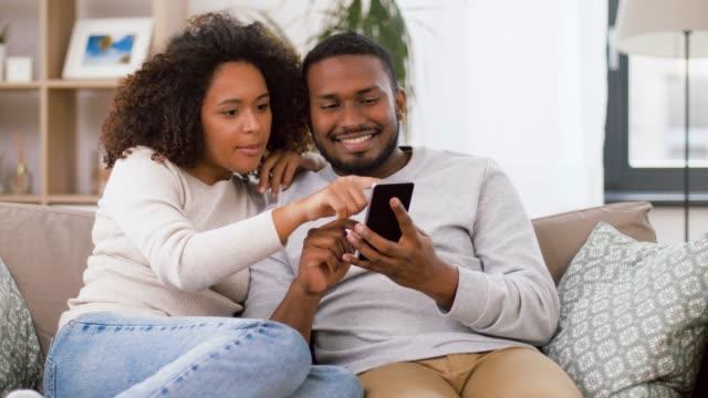 afroamerikanskt par med smartphone hemma video