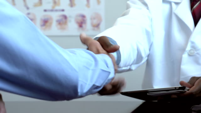 African American doctor shaking hands with patient, close up video