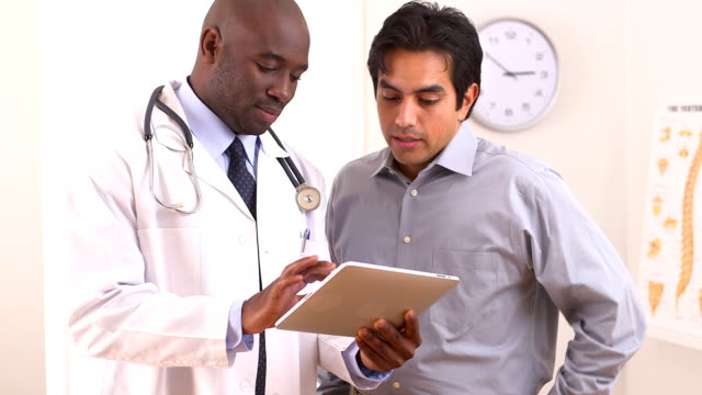 African American doctor using tablet pc with Hispanic patient