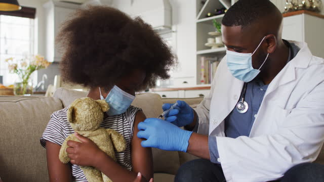 African american doctor wearing face mask injection covid-19 vaccine to girl at home African american doctor wearing face mask injection covid-19 vaccine to girl at home. concept of corona virus vaccine and treatment during pandemic. covid 19 vaccine stock videos & royalty-free footage