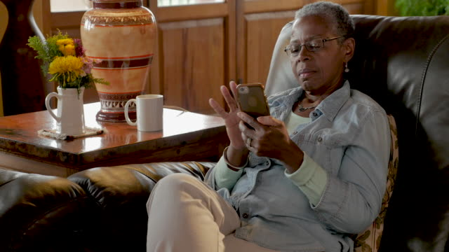 African American elderly woman relaxing with her mobile phone