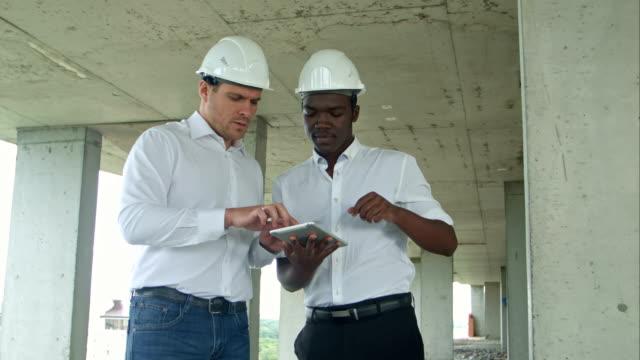 Afro americano arquitecto ingeniero y caucasine uso de tableta digital y usar cascos de seguridad en obra - vídeo