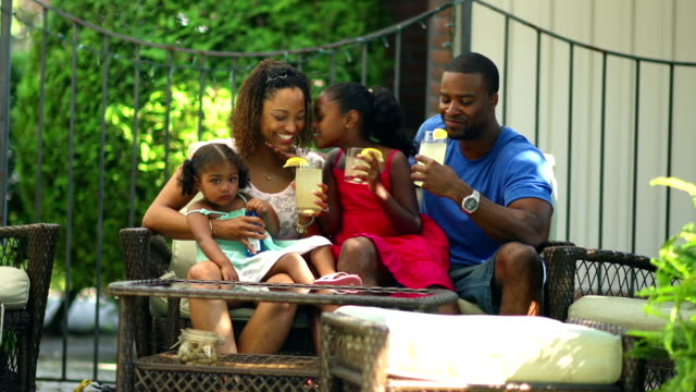 African American family drinking lemonade outdoors on a couch together video