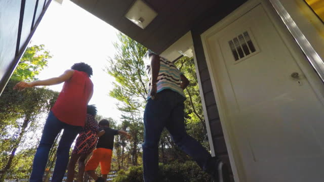 african american family leaving the house - scendere video stock e b–roll