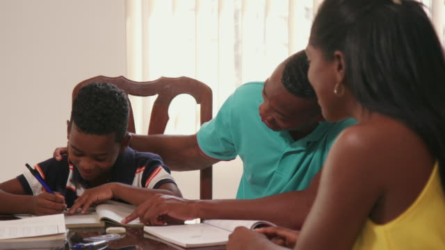 African American Family Mom Smiling Dad Helping Son With Homework - vídeo