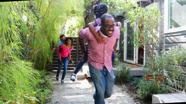 African American Family Piggy Backing Through the Garden video