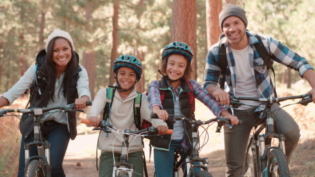 African American family sitting on bikes in forest, close up video