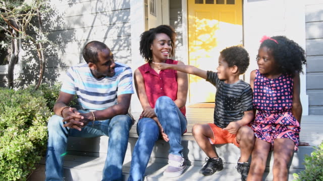 African American family sitting on doorstep talking and smiling video