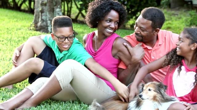 愛犬と芝生の上に座っているアフリカ系アメリカ人の家族 ビデオ