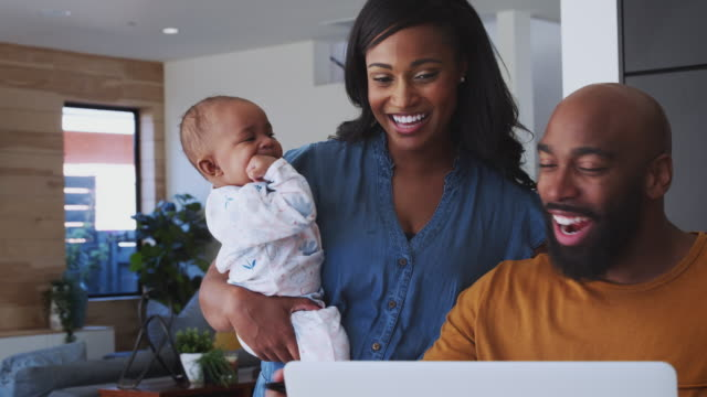 African American Family With Baby Daughter Using Laptop To Check Finances At Home