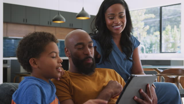 African American Family With Son Sitting On Sofa At Home Using Digital Tablet