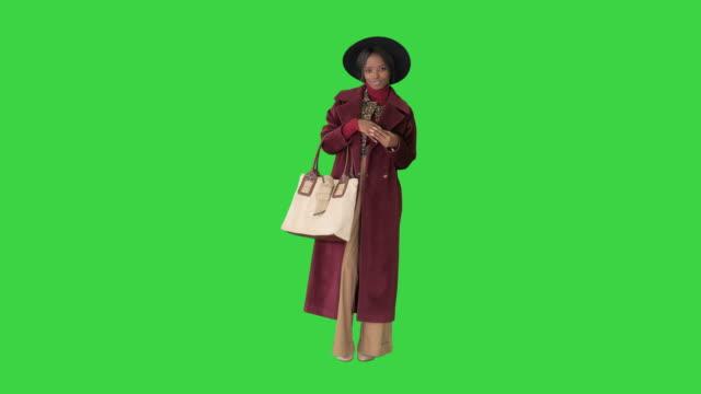 vídeos y material grabado en eventos de stock de chica de moda afroamericana en abrigo y sombrero negro posando con un bolso en una pantalla verde, chroma key - abrigo
