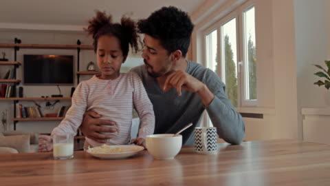 vídeos y material grabado en eventos de stock de americano africano padre e hija que se divierten durante la hora del desayuno en casa. - desayuno