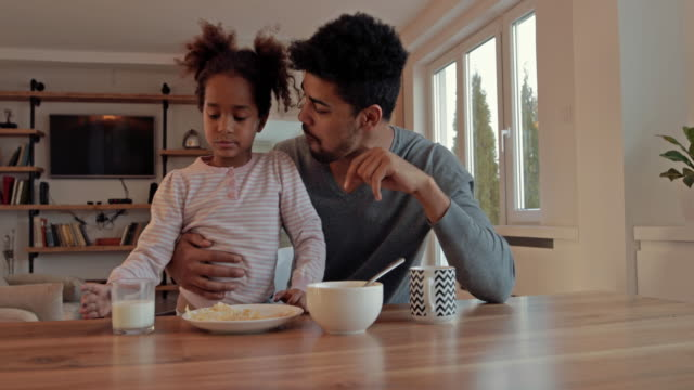 African American father and daughter having fun during breakfast time at home. video